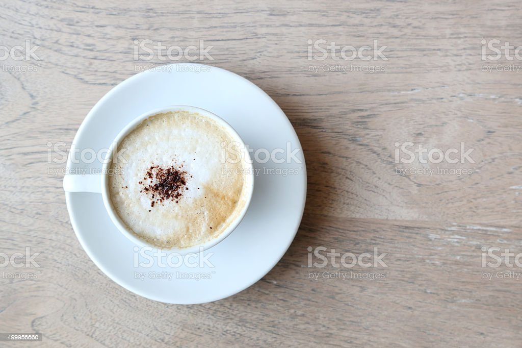 Cup of cappuccino with foam on the wooden table stock photo