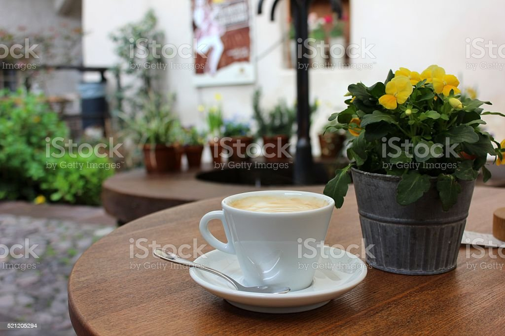 Cup of cappuccino with pansies in pot on table stock photo