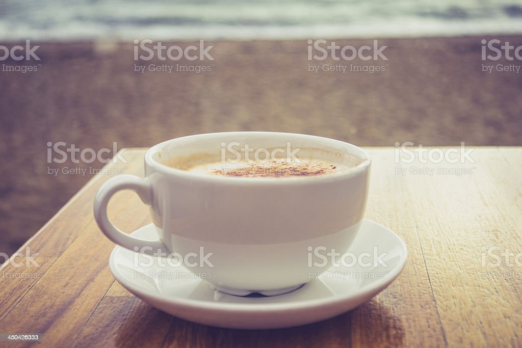 Cup of cappucino by the sea royalty-free stock photo