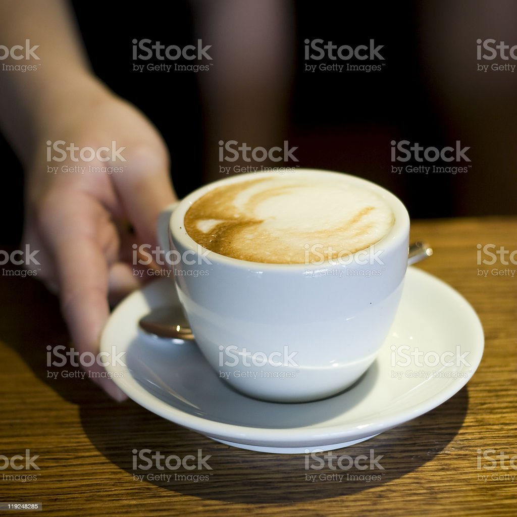 Cup of cappucino serving by waiter royalty-free stock photo