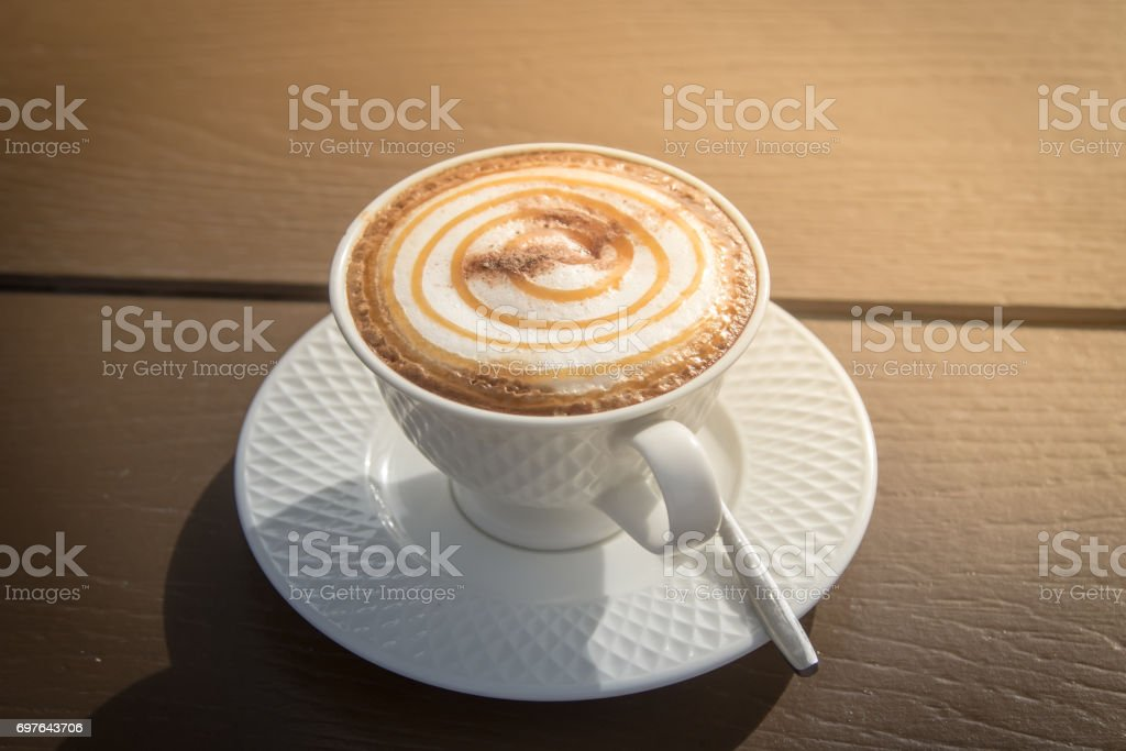 A cup of Caramel Macchiato coffee on wooden table in the morning. stock photo