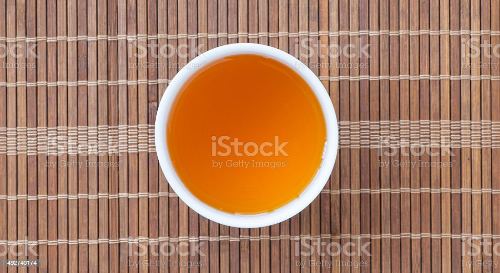 Cup of Chinese hot tea on bamboo mat background stock photo