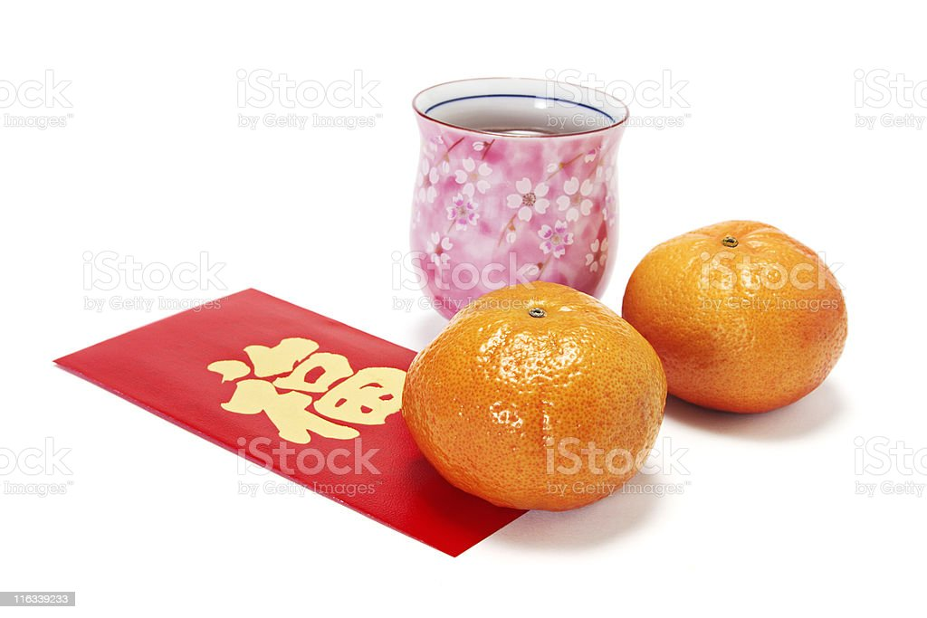 Cup of Chinese Tea with Mandarins on Red Packet royalty-free stock photo