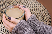 cup of cocoa in hands with nail polish knitted sweater