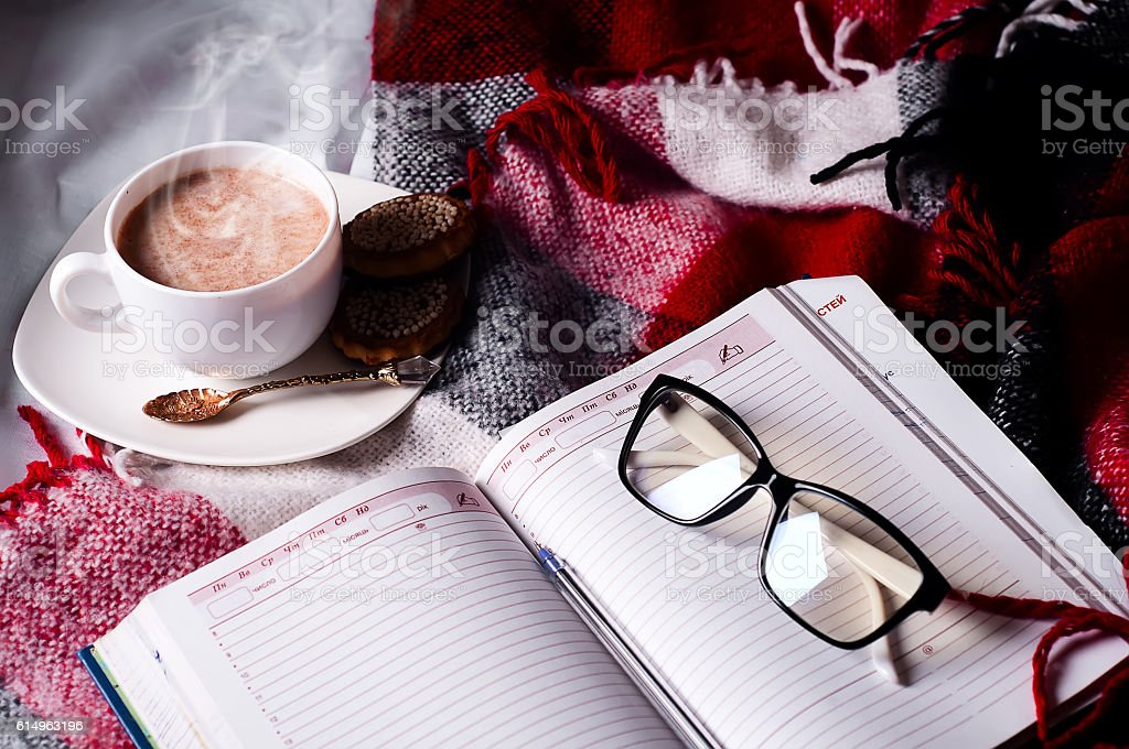 Cup of cocoa staying on open book stock photo