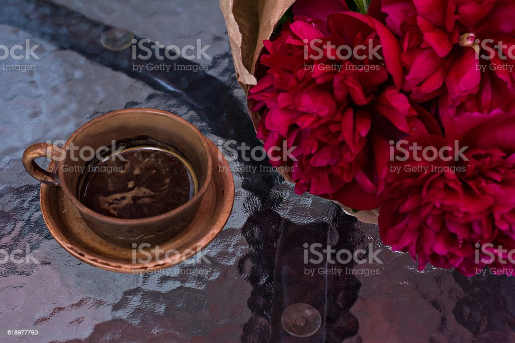 cup of coffee and a bouquet of peonies stock photo