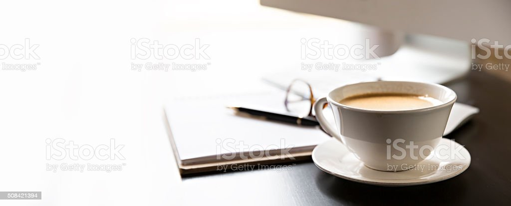 Cup of coffee and a computer at work . stock photo
