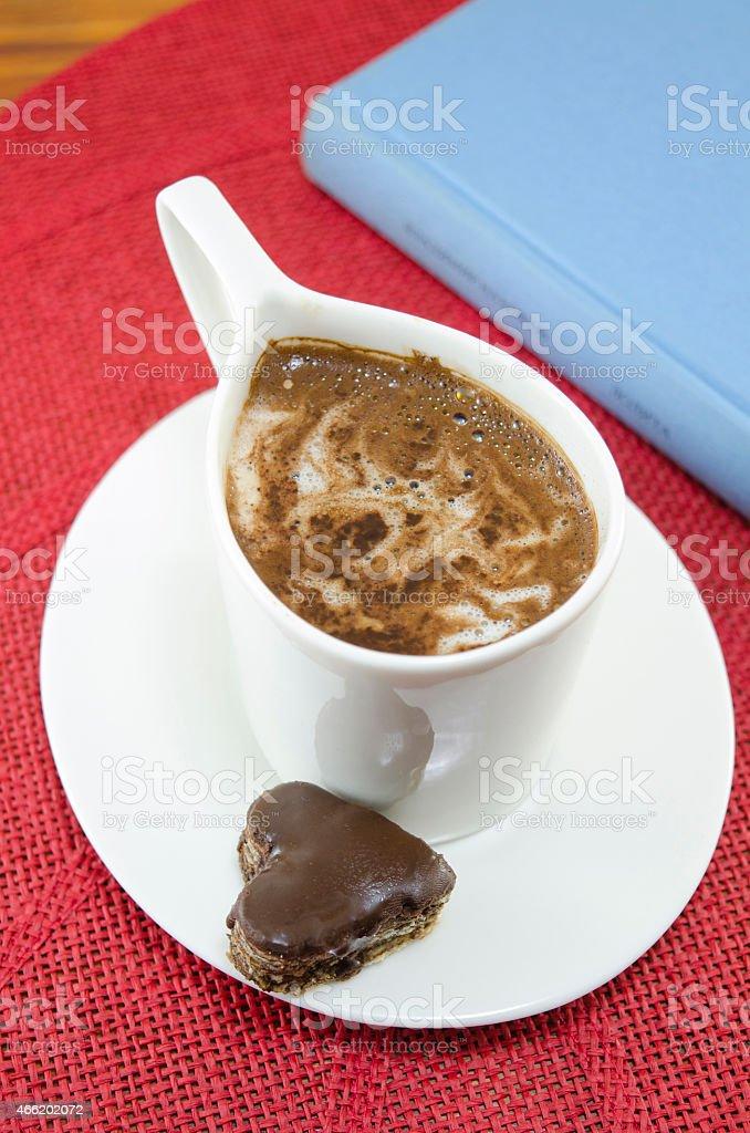 Cup of coffee and a heart shaped chocolate royalty-free stock photo