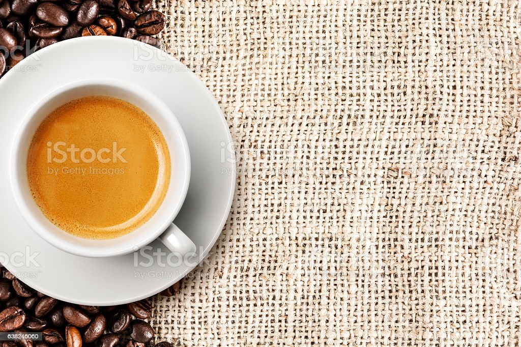 Cup of coffee and beans on rough hemp sack stock photo