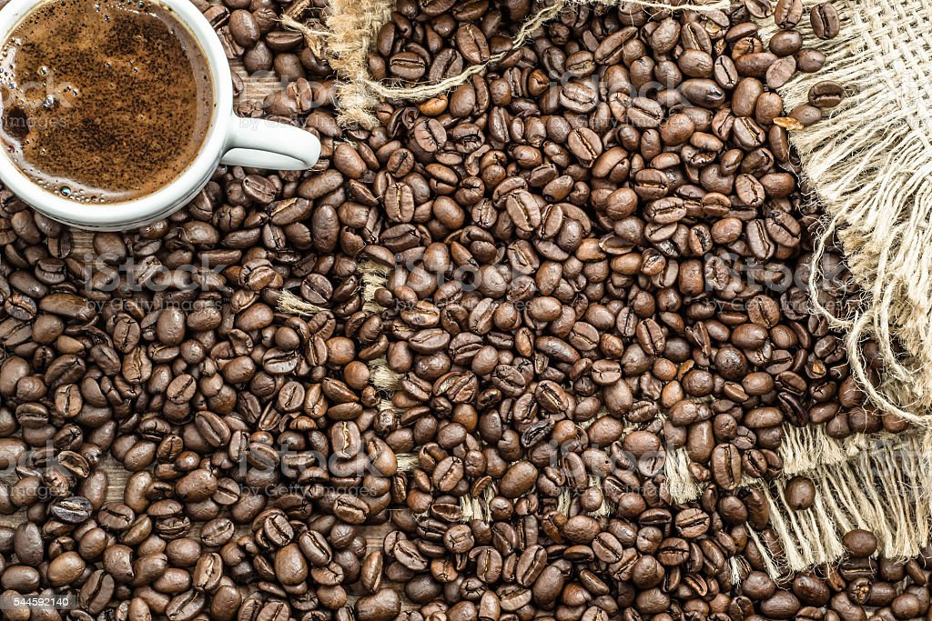 Cup of coffee and black coffee beans on wooden table. stock photo