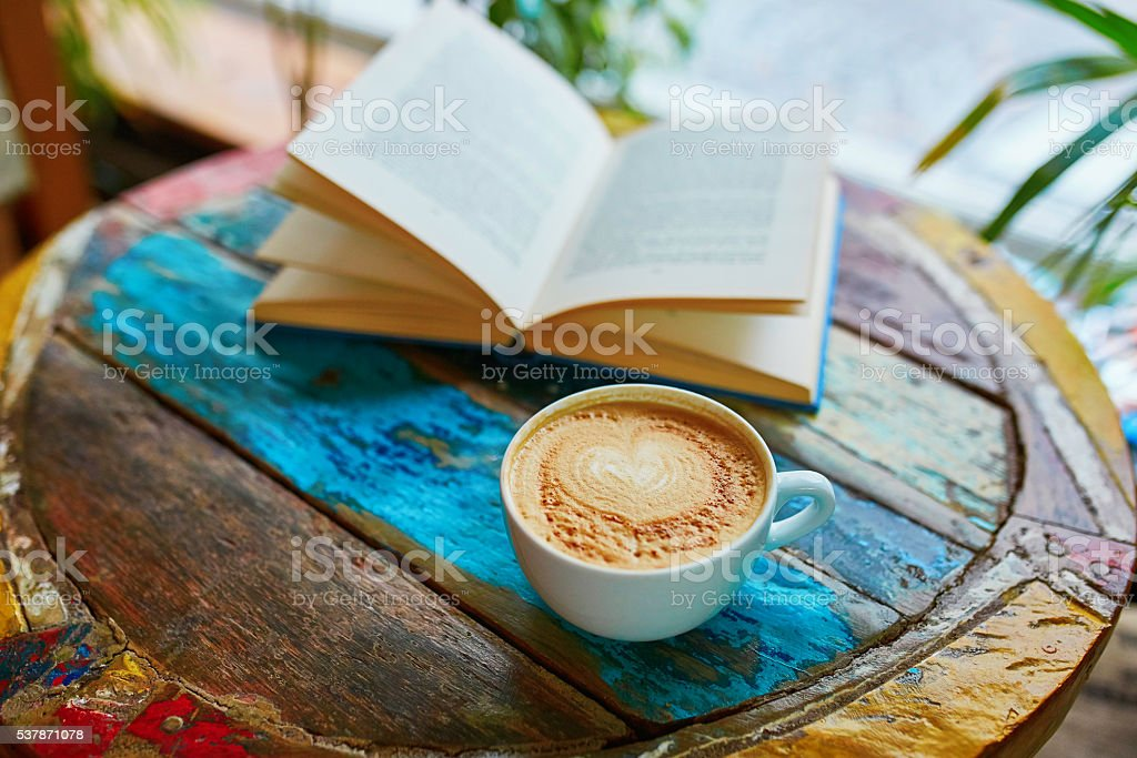 Cup of coffee and book on a wooden table stock photo