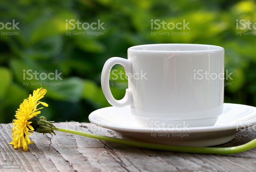 Cup of coffee and flower on wooden table.