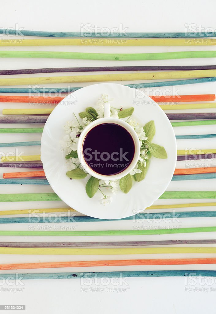 cup of coffee and flowers on a colored striped background stock photo