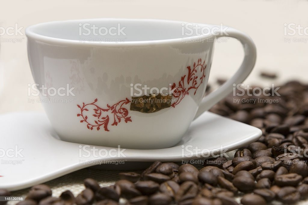 Cup of coffee and grains over sackcloth royalty-free stock photo
