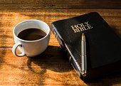 Cup of coffee and holy bible on wooden table