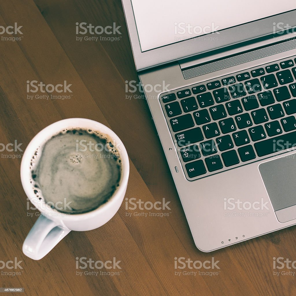 Cup of coffee and laptop on wooden table stock photo