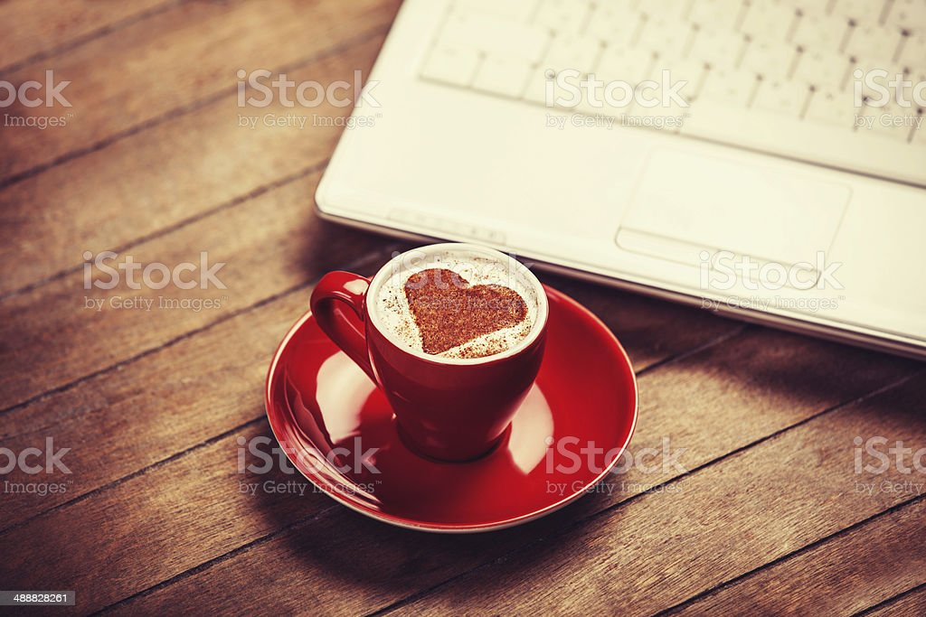 Cup of coffee and laptop on wooden table. stock photo
