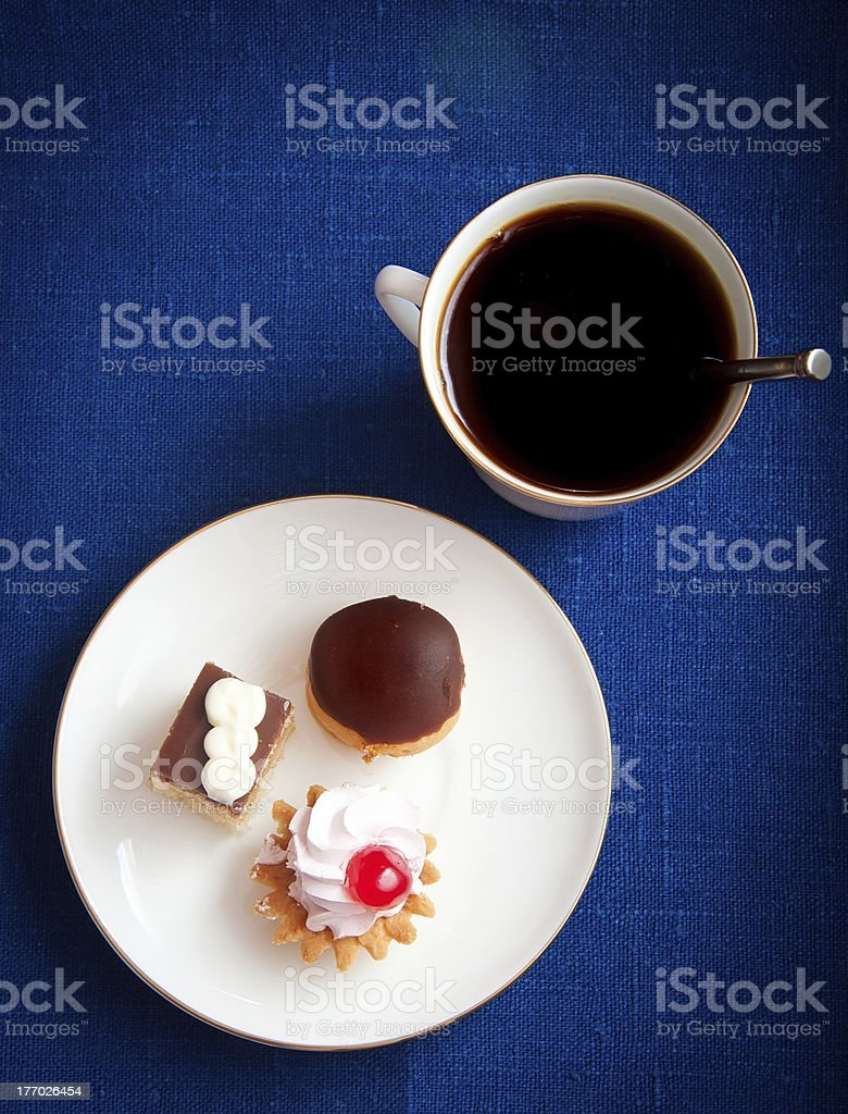 Cup of coffee and pastries on blue tablecloth royalty-free stock photo