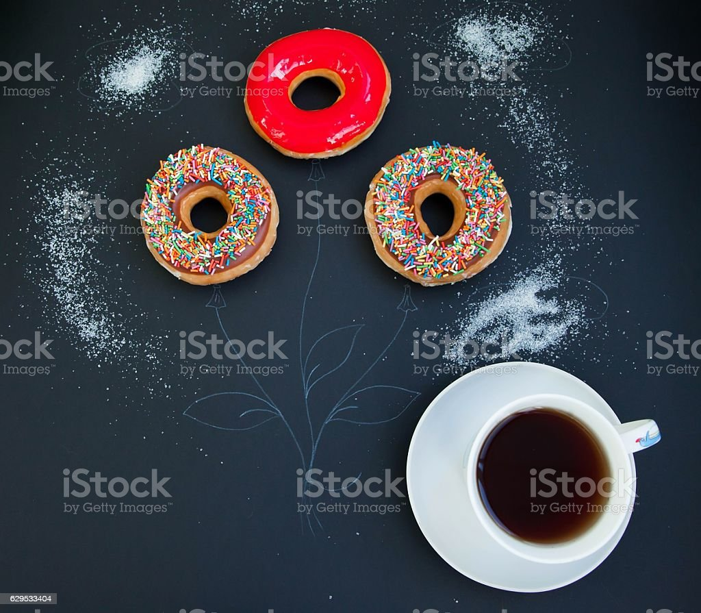 Cup of coffee and three colorful donuts royalty-free stock photo