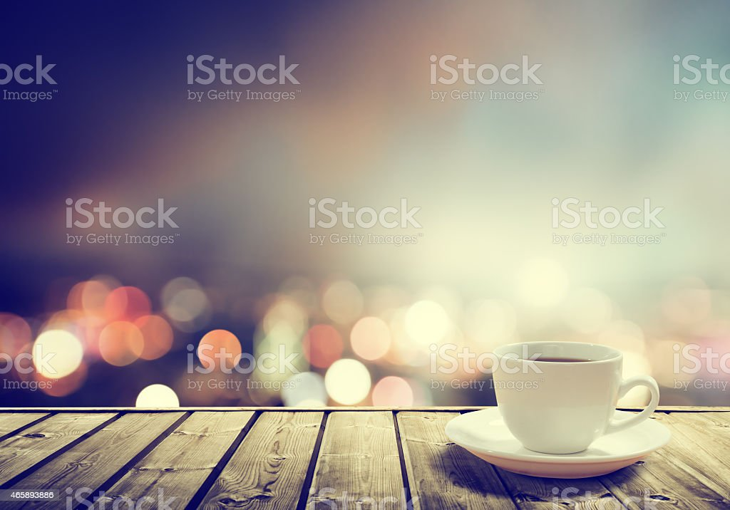 A cup of coffee at night on a wooden table stock photo