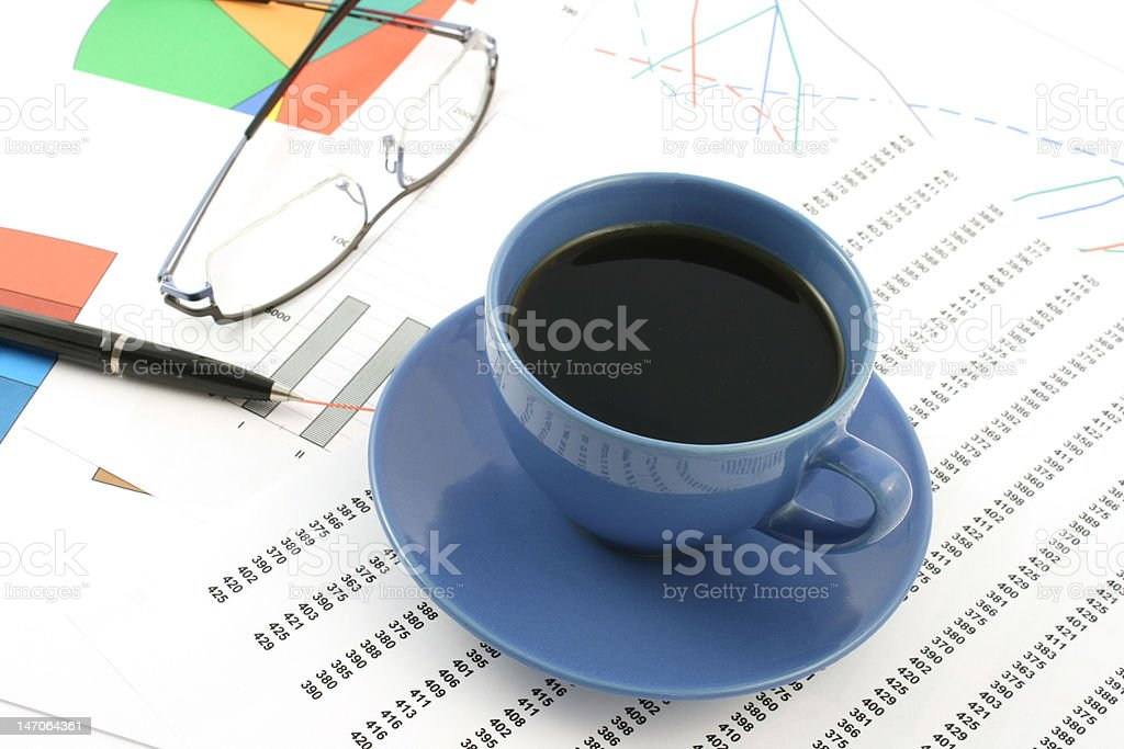 cup of coffee, ballpoint pen and glasses on earning graphs royalty-free stock photo
