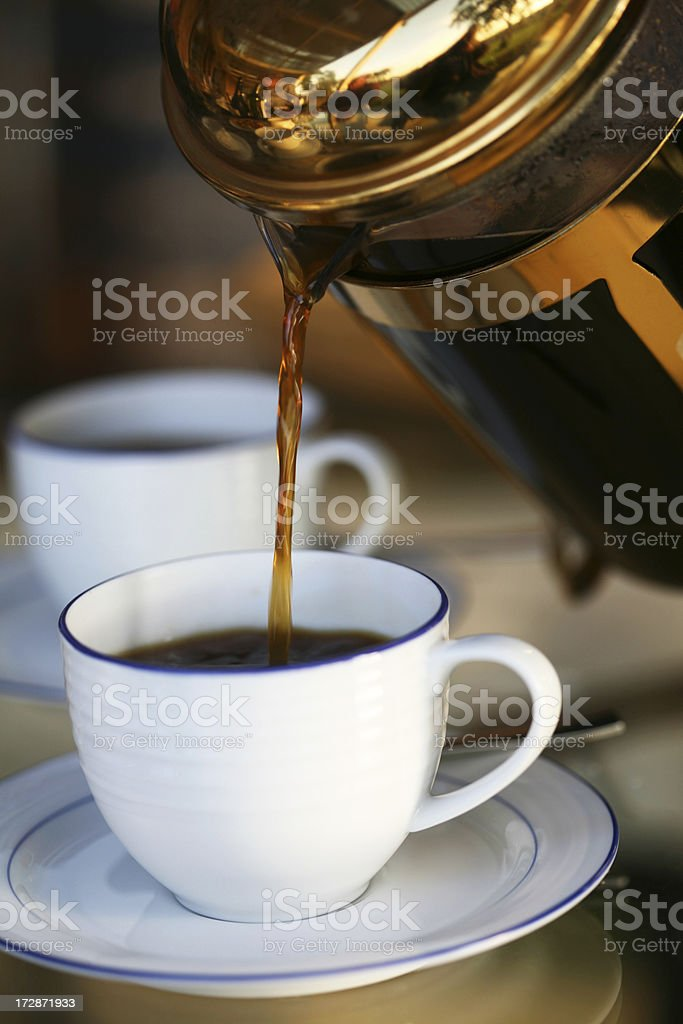 A cup of coffee being poured at a restaurant stock photo