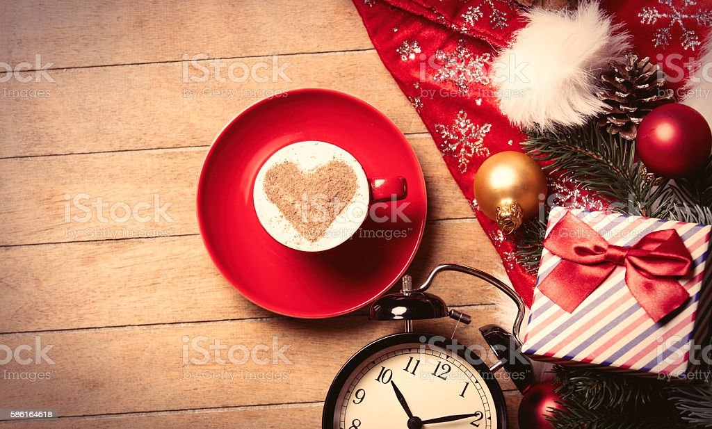 cup of coffee, clock and christmas decorations stock photo