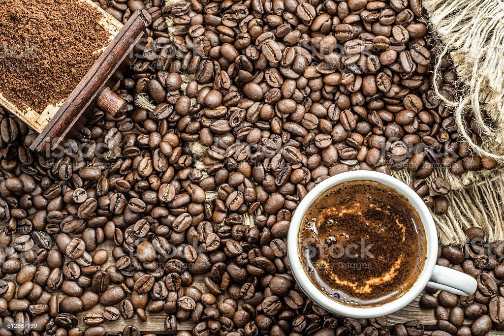 Cup of coffee, coffee powder and coffee beans on table. stock photo
