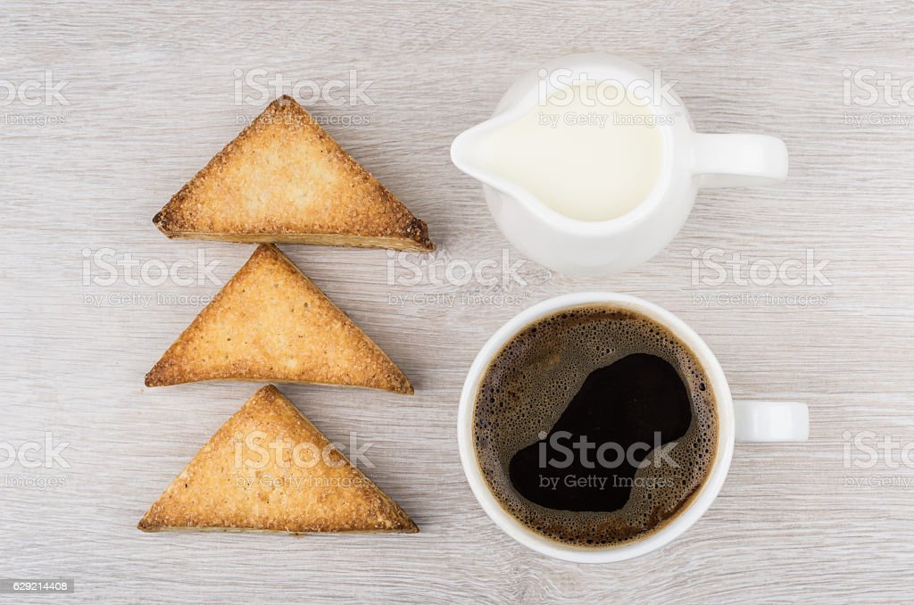 Cup of coffee, flaky cookies and milk on table stock photo