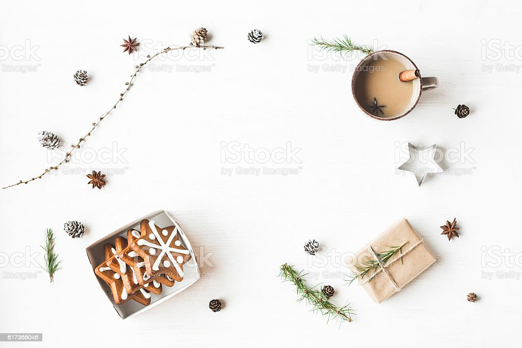 Cup of coffee, gift, larch branches, cinnamon sticks, christmas cookies stock photo