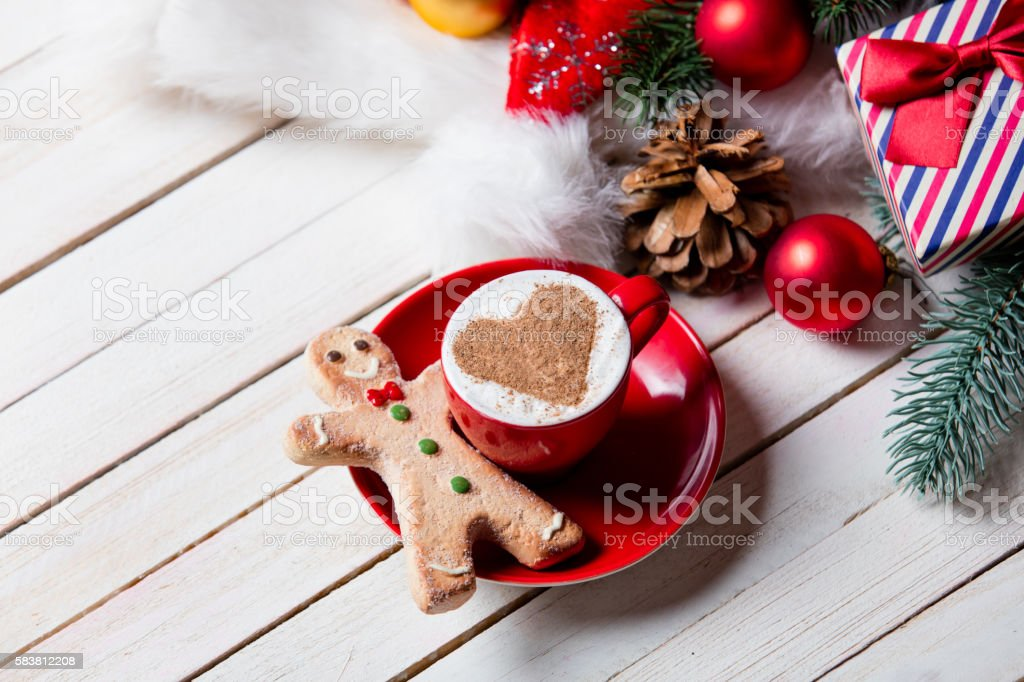 cup of coffee, gingerbread man and christmas decorations stock photo