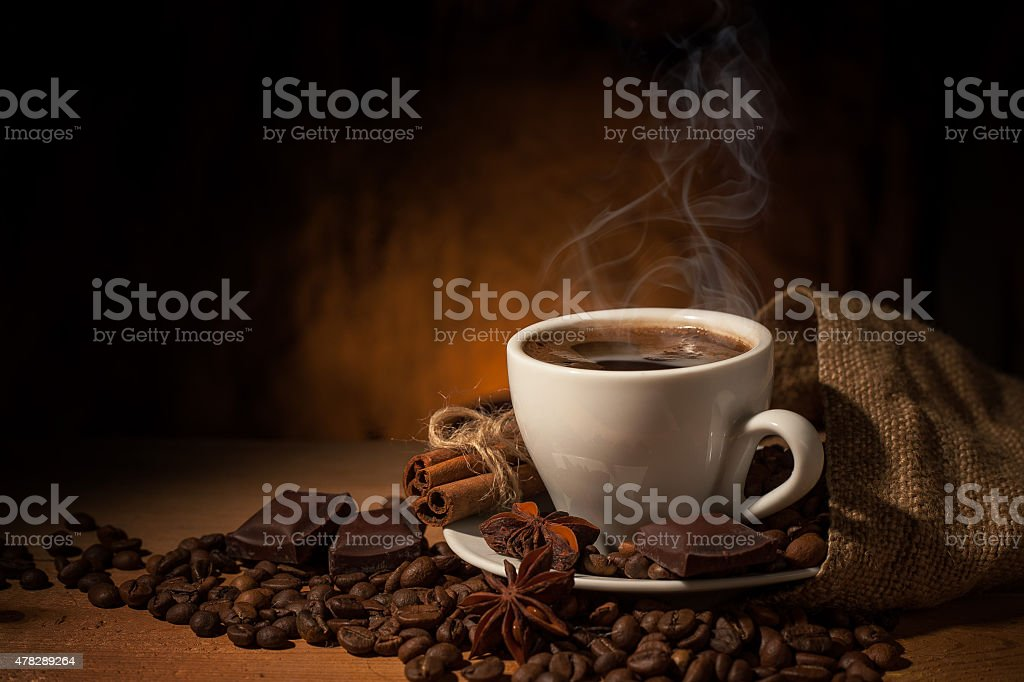 Cup of coffee in coffee beans on brown background stock photo