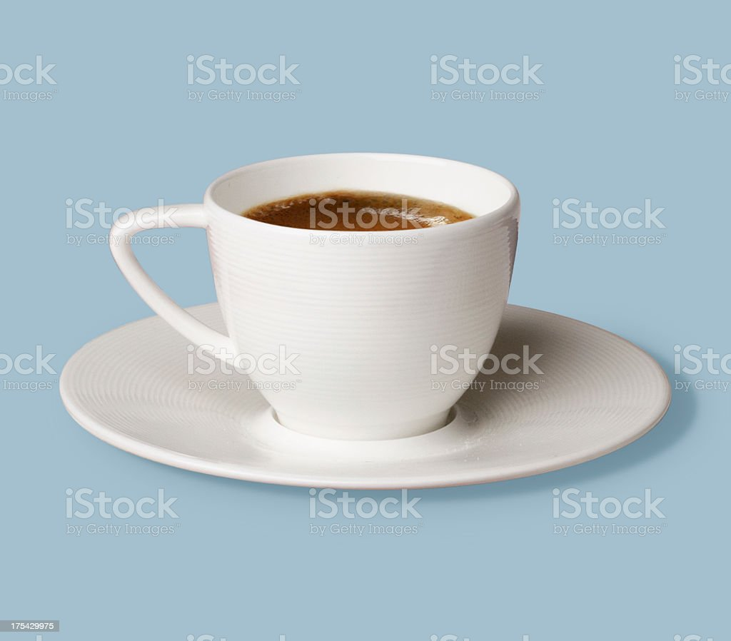 Cup of coffee in white mug on a white plate against blue royalty-free stock photo