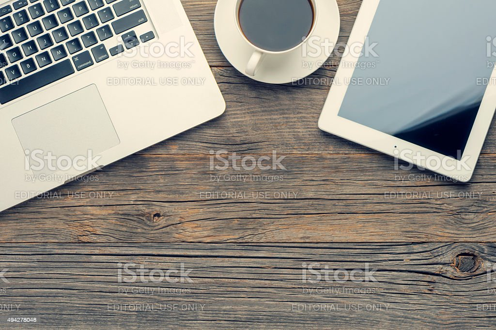 Cup of coffee, laptop and digital tablet on wooden table. stock photo