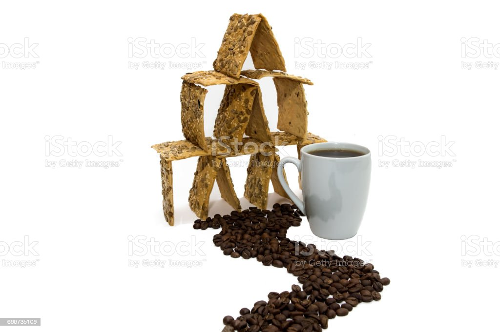 A cup of coffee next to the cookie house, the road from the grains of the coffee. stock photo
