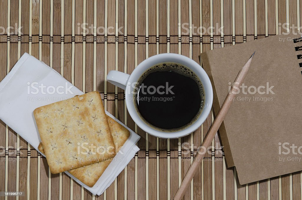 cup of coffee notebook with pencil and biskit stock photo