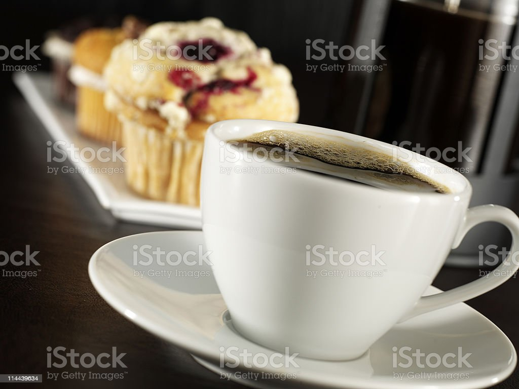 A cup of coffee on a saucer with muffins on a dish royalty-free stock photo