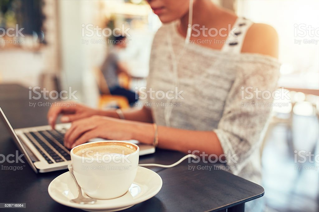 Cup of coffee on cafe table with a woman stock photo