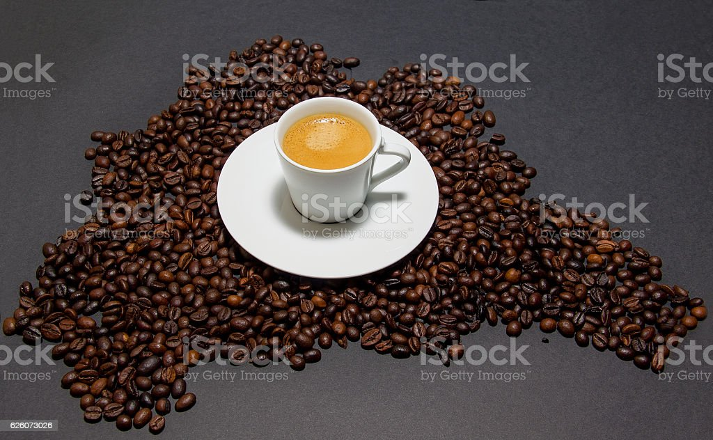Cup of coffee on coffee beans suggesting map of Brasil stock photo