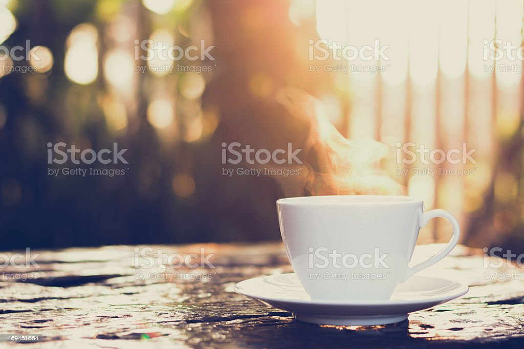 Cup of coffee on old wood table - vintage tone stock photo