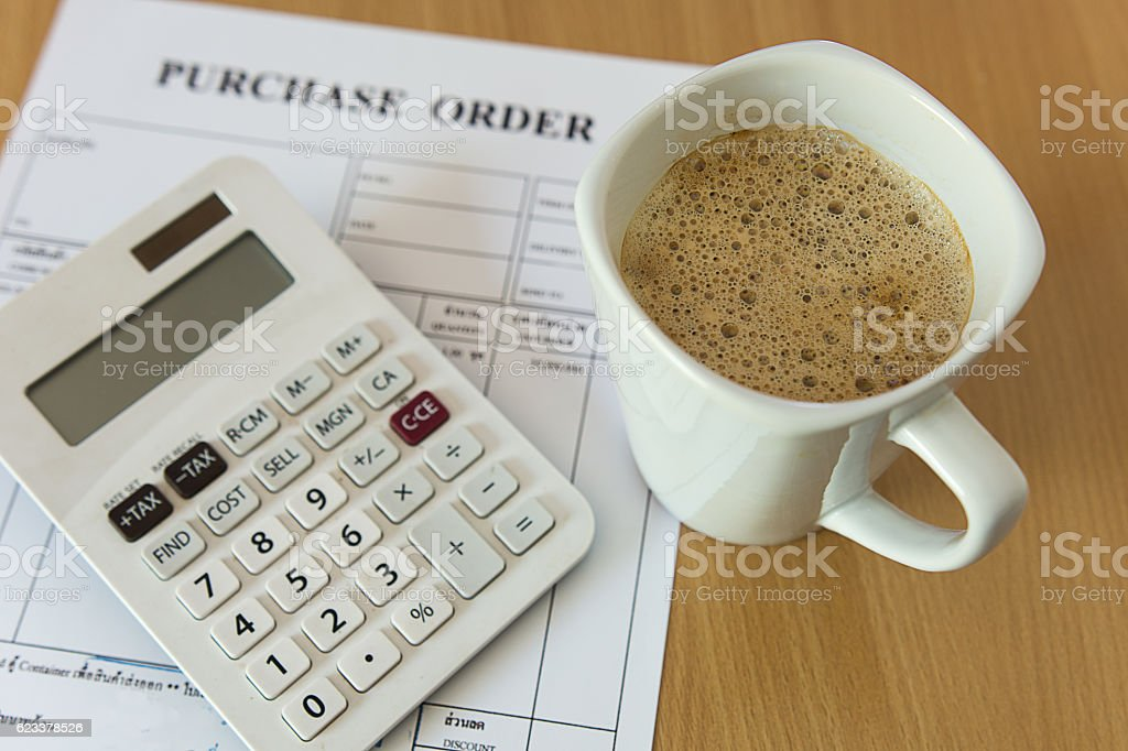 cup of coffee on purchase order form stock photo