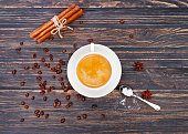 Cup of coffee on saucer with spoon. Vanilla sticks. Star