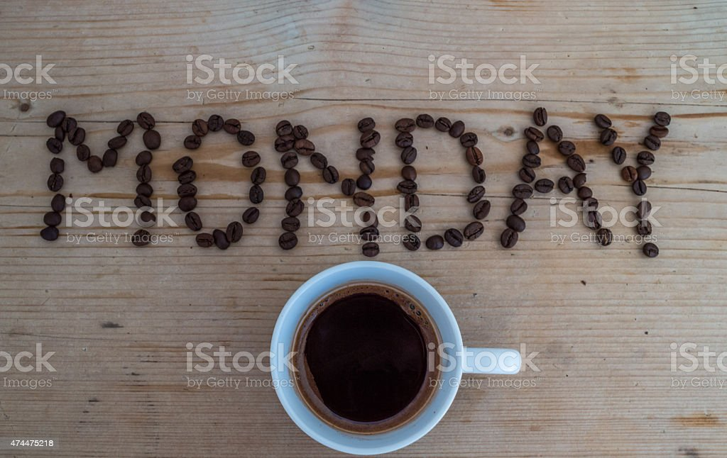 Cup of coffee on wooden background and monday coffee beans stock photo