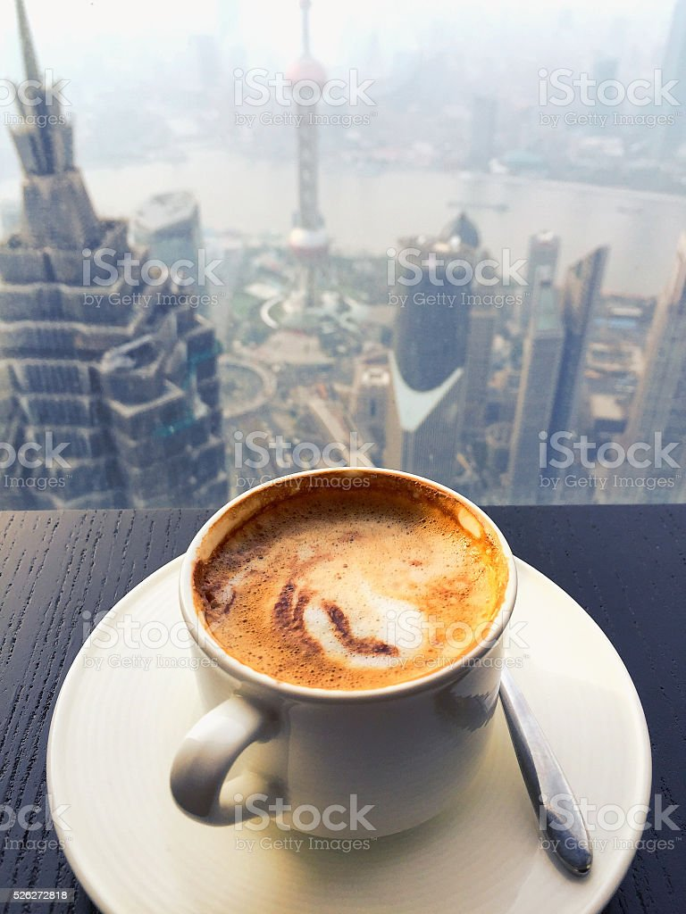 Cup of coffee on wooden table with view of skyscrapers stock photo