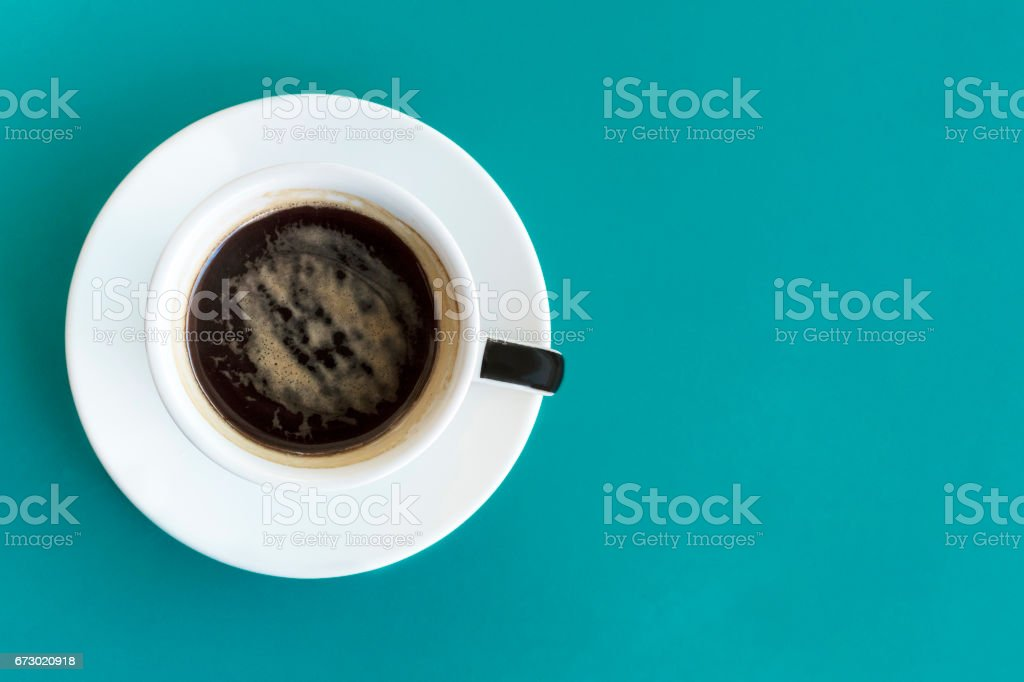 Cup of coffee, shot from above on vibrant turquoise stock photo