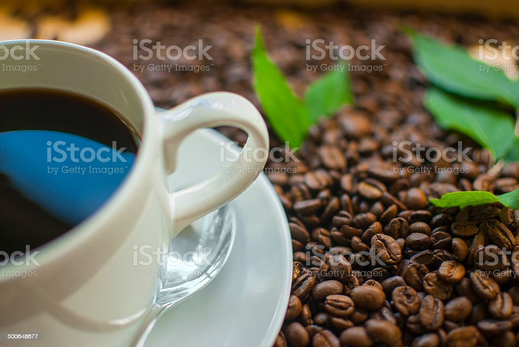 Cup of coffee sitting on wood tray surrounded by coffee beans royalty-free stock photo
