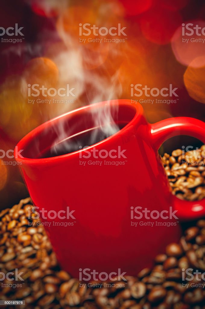 Cup of coffee standing on coffee beans stock photo