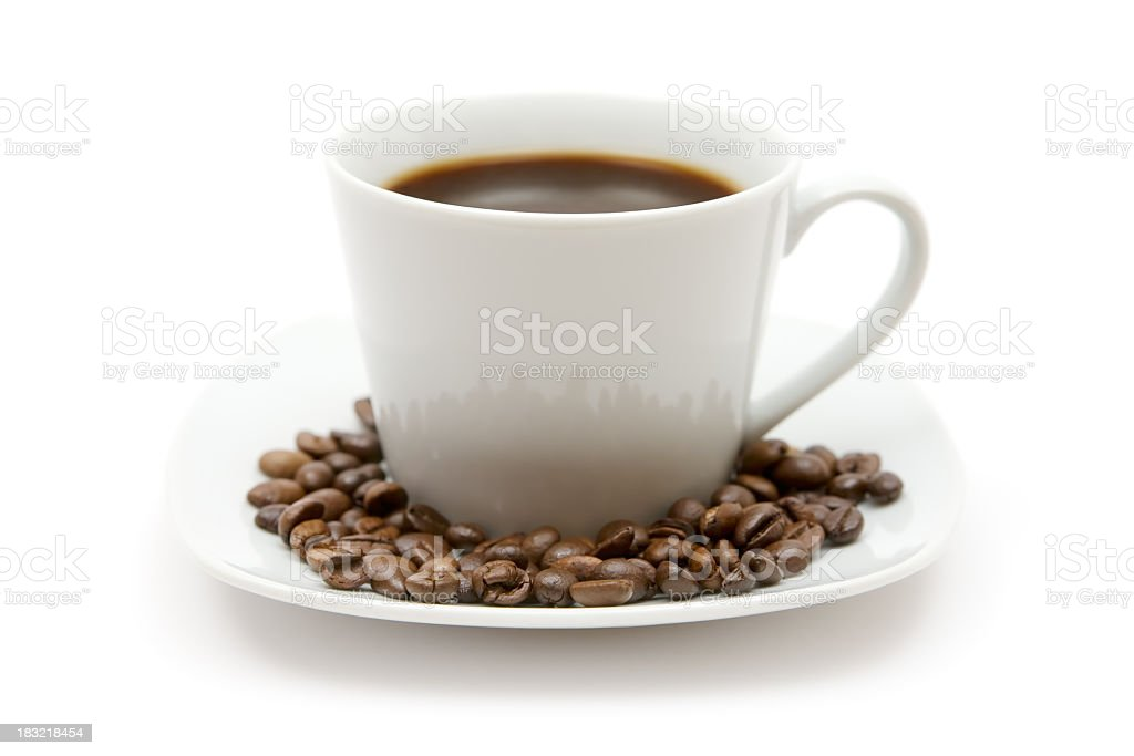 Cup of coffee surrounded by coffee beans on white saucer stock photo