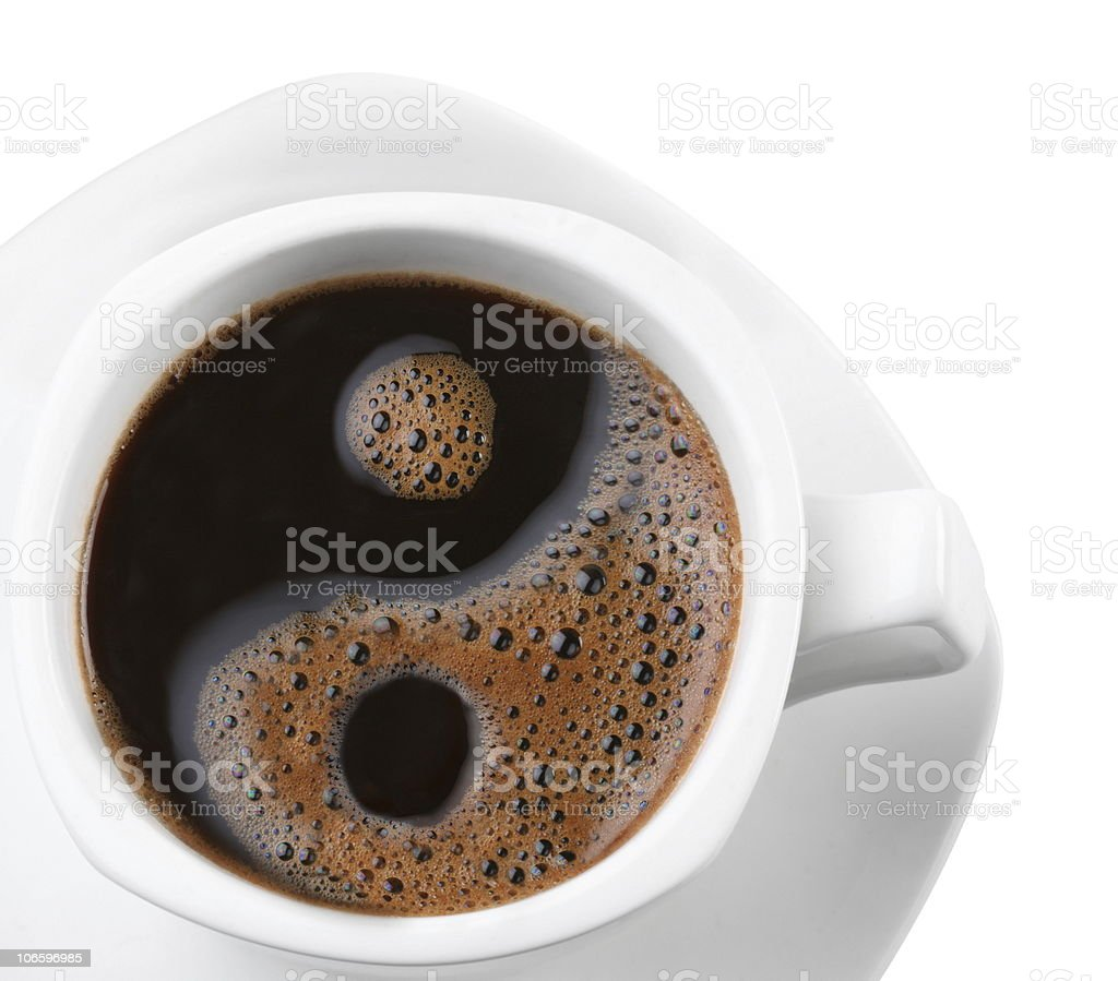 A cup of coffee with a yin and yang symbol in it  stock photo