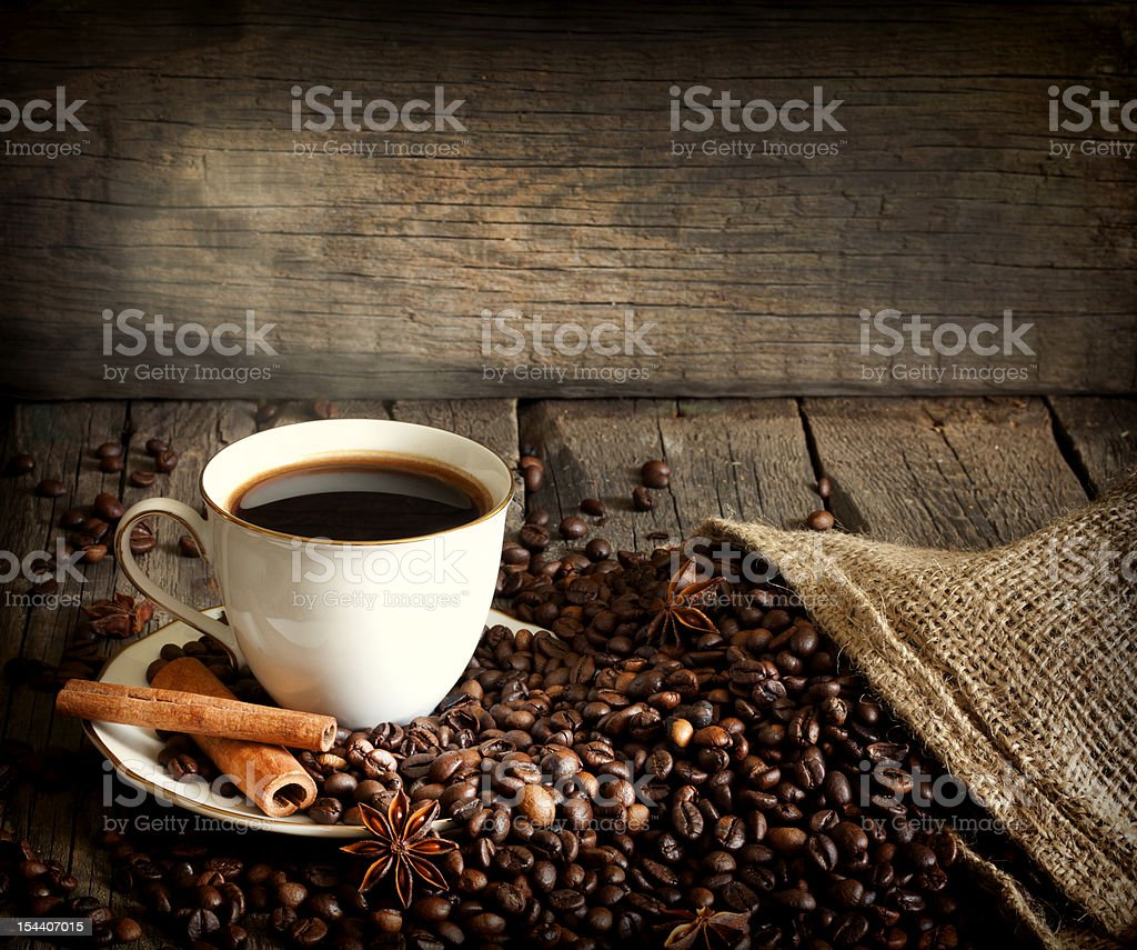 Cup of coffee with beans and cinnamon royalty-free stock photo